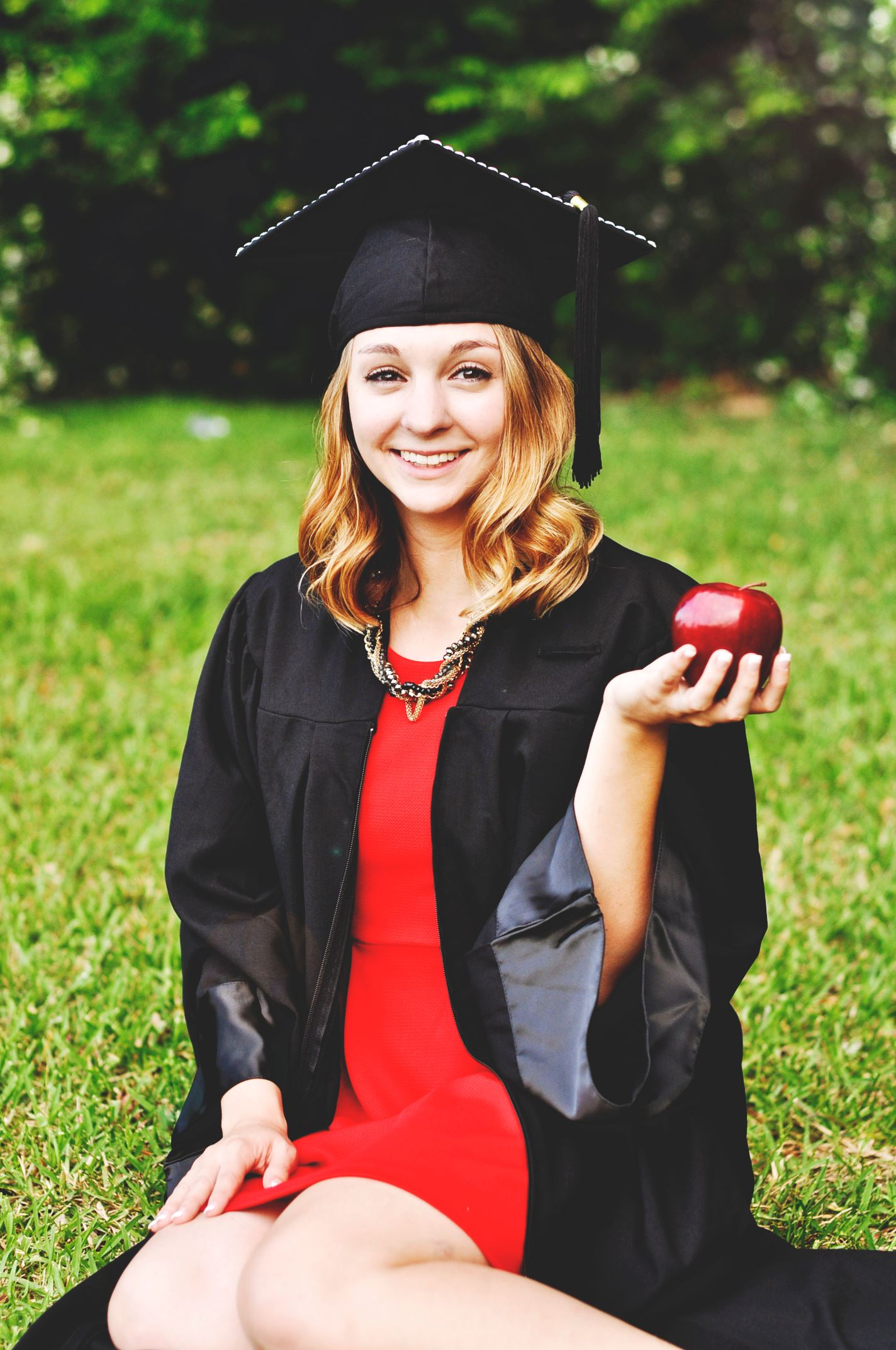 Woman in graduation gown holding an apple.