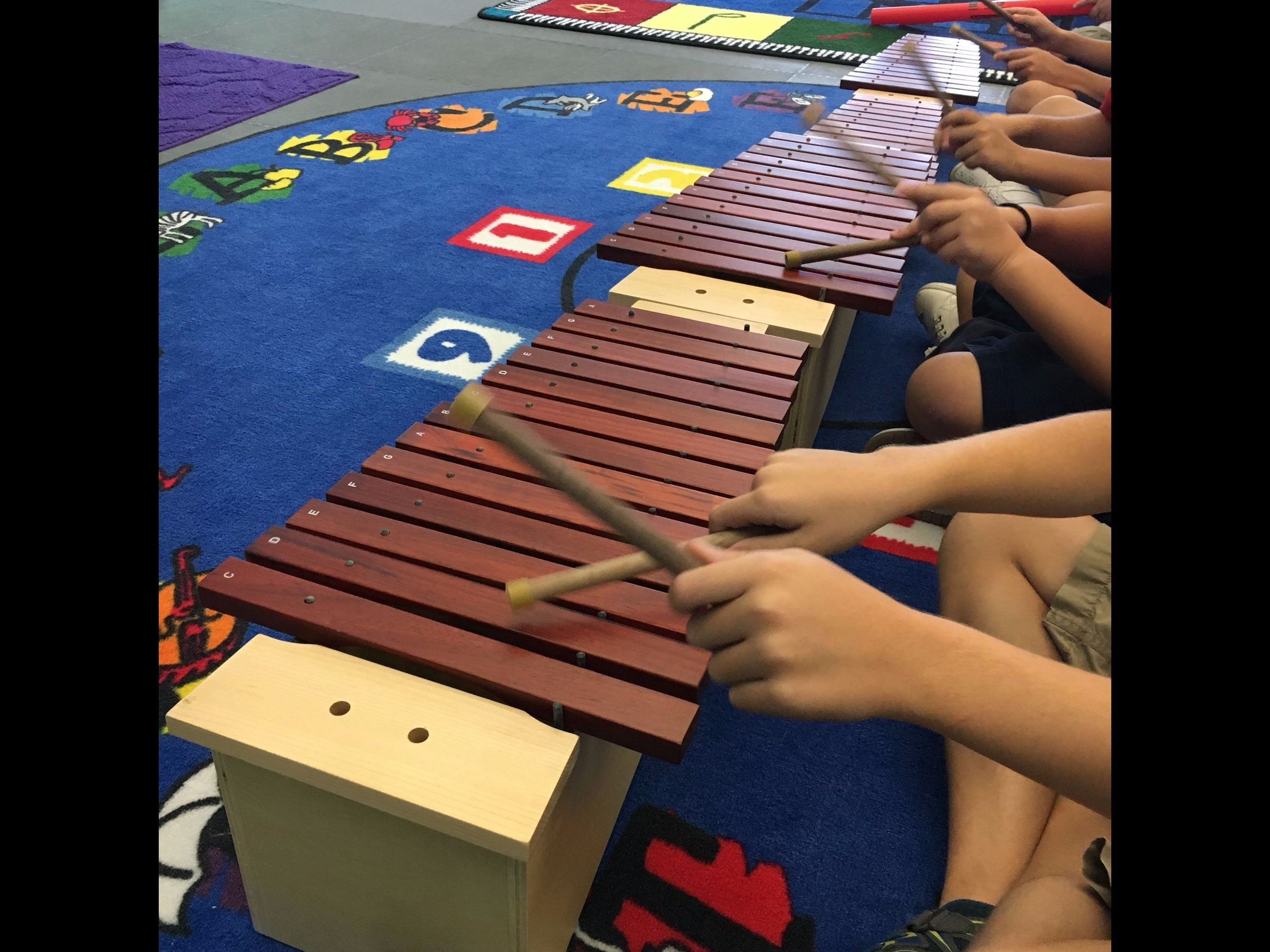 Students making music with xylophones.