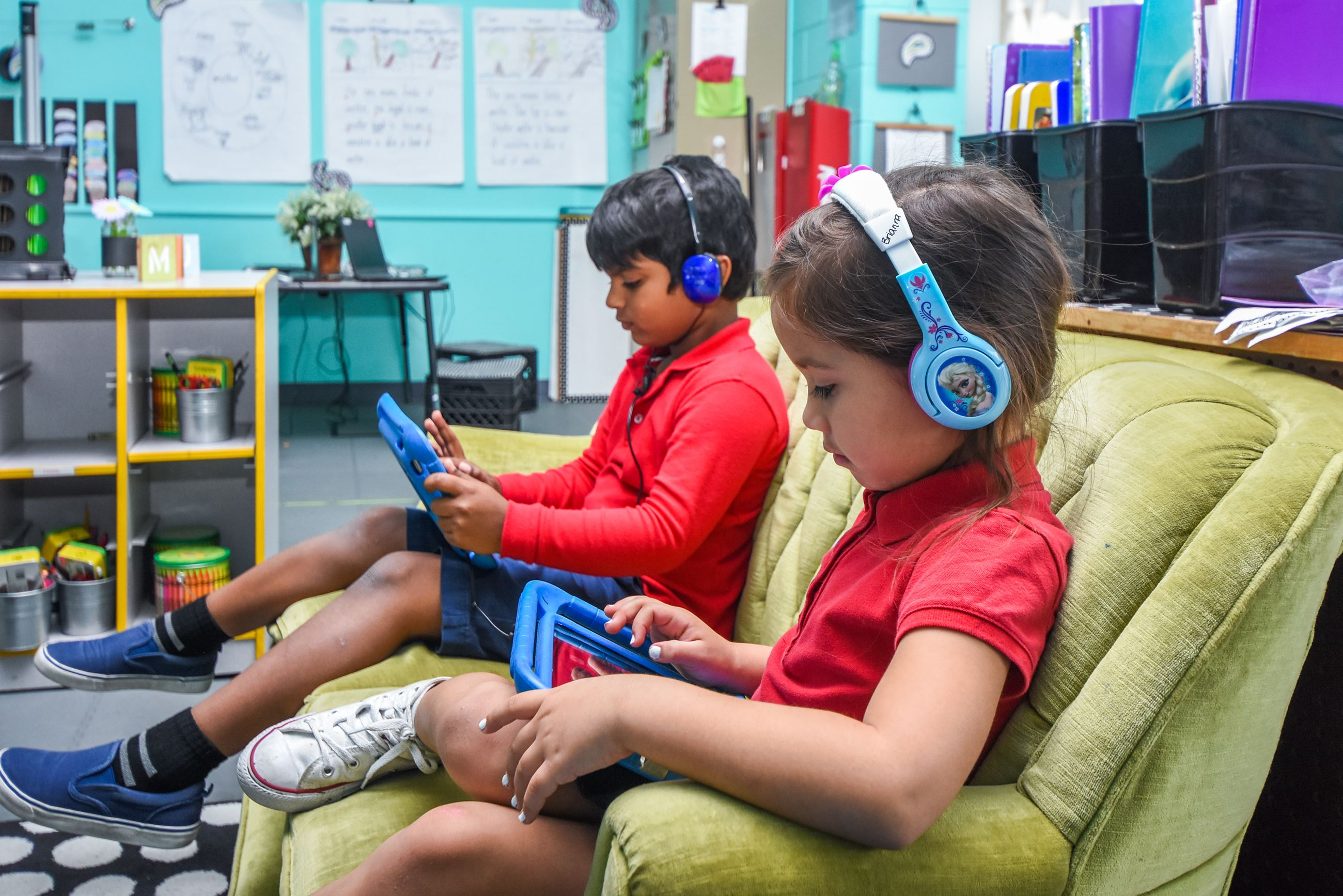A girl and a boy sitting on a couch in a classroom.  Both wearing headphones and working on iPads.